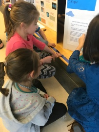 Showing her friends her project.